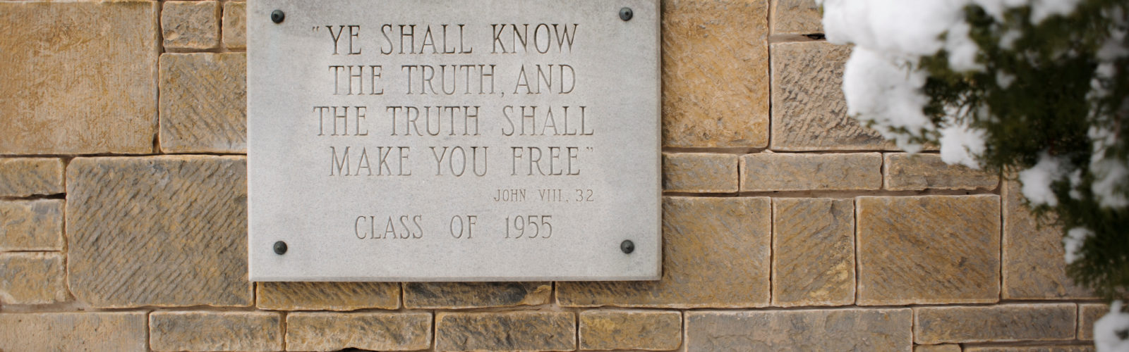 "Stone plaque reading, ""Ye shall know the truth, and the truth shall make you free."""